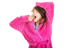 Beautiful yawning woman in pink bathrobe. Royalty Free Stock Images