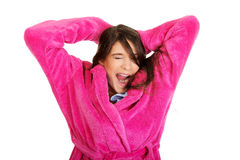 Beautiful yawning woman in pink bathrobe. Stock Photos