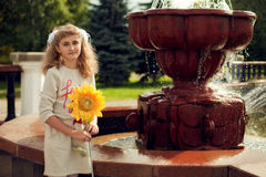 Beautiful 10 years old girl standing near a fountain, holding a. Sunflower walking around the city Royalty Free Stock Photos