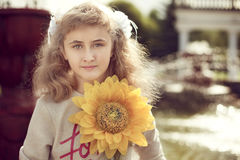 Beautiful 10 years old girl standing near a fountain, holding a. Sunflower walking around the city Stock Photo