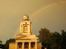 Old yellow church and rainbow, Latvia stock photography