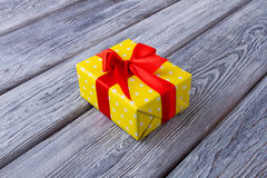 Beautiful yellow gift box with a red ribbon. Stock Photography