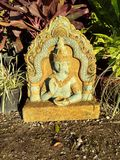 Beautiful yellow green & emerald one sided buddha statue. In front of other pretty plants on the ground Royalty Free Stock Image
