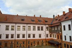 Beautiful yellow historical medieval European low-rise buildings with a red tile roof gable and rectangular windows with bars royalty free stock photography