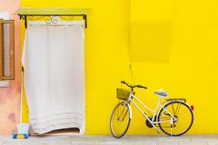 Beautiful yellow house with a bicycle. Colorful houses in Burano island near Venice, Italy. Stock Photo