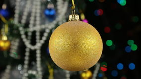 Beautiful yellow New Year and Christmas decoration ball heavily swinging on rope. As a background stock video