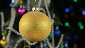 Beautiful yellow New Year and Christmas decoration ball swinging on rope. Against a background of a rotating Christmas tree and a flashing garland stock video footage