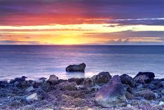 Beautiful yellow, orange, red and blue sunset seascape at Mull of Galloway rocky coast in Ayrshire royalty free stock photo