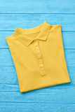 Beautiful yellow polo t-shirt isolated. New trendy item for summer resort, blue background Stock Photo