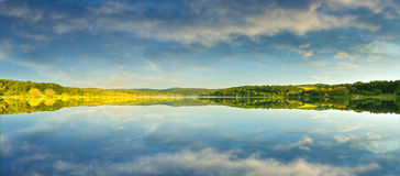 Beautiful yellow rape field, reflected in the lake Stock Images