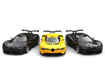 Beautiful yellow super car with two black sports cars on each side Stock Photos