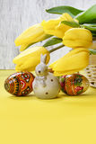 Beautiful yellow tulips, easter eggs and ceramic rabbit Stock Images