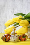 Beautiful yellow tulips, easter eggs and ceramic rabbit Stock Photos