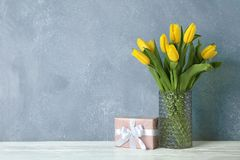 Beautiful yellow tulips in glass vase on wooden table stock photo