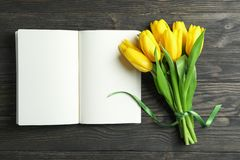 Beautiful yellow tulips and notebook on wooden background. Blogging concept royalty free stock photos