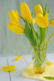 Beautiful yellow tulips in vase on rustic table Stock Photos