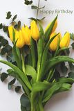 Beautiful yellow tulips on a white table, inscription happy birthday.  stock photography