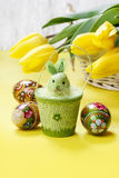Beautiful yellow tulips in white wicker basket and easter eggs Stock Images