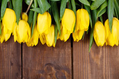 Beautiful yellow tulips on wooden background. Top view, copy space Royalty Free Stock Image