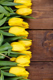 Beautiful yellow tulips on wooden background. Top view, copy space Royalty Free Stock Photo