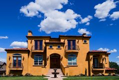 Beautiful yellow villa. With white clouds above Royalty Free Stock Image