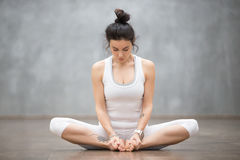 Beautiful Yoga: Bound angle pose. Portrait of beautiful young woman with floral tattoos working out against grey wall, doing yoga or pilates exercise, sitting in Royalty Free Stock Photos