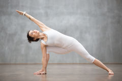 Beautiful Yoga: extended side angle pose. Portrait of beautiful young woman wearing white sportswear working out against grey wall, doing yoga or pilates Royalty Free Stock Photo