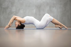 Beautiful Yoga: Fish pose. Beautiful young woman wearing white sportswear working out in fitness club against grey wall, doing yoga or pilates exercise Stock Photography