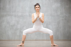 Beautiful Yoga: Goddess pose. Portrait of beautiful young woman wearing white sportswear working out against grey wall, doing yoga or pilates exercise. Standing Royalty Free Stock Photo