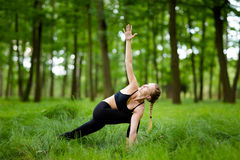 Beautiful yoga session in woods. Nature yoga session in beautiful green polish woods, between trees. Twisted triangle pose, Parivrtta bikram Trikonasana Royalty Free Stock Photos