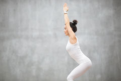 Beautiful Yoga: Utkatasana pose. Side view portrait of beautiful young woman wearing white sportswear working out against grey wall, doing yoga or pilates Royalty Free Stock Photography