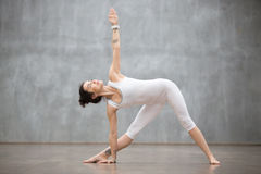Beautiful Yoga: Utthita Trikonasana, extended triangle pose. Profile portrait of beautiful young woman wearing white sportswear working out against grey wall Stock Photos