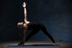 Beautiful Yoga Woman Doing Extended Triangle Pose. Beautiful sporty fit young woman in black sportswear working out indoors against grunge dark blue wall. Model royalty free stock photography