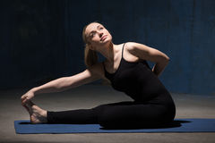 Beautiful Yoga Woman sitting in Half Bound Lotus Forward Bend Royalty Free Stock Photo