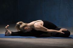 Beautiful Yoga Woman sitting in Head to Knee Forward Bend Pose royalty free stock photography