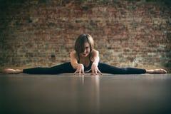 Beautiful yogini woman practices yoga asana Samakonasana Straight angle posture in the yoga studio on a brick wall background. Beautiful yogini fit woman royalty free stock photos
