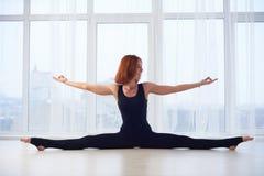 Beautiful yogini woman practices yoga asana Samakonasana Straight angle posture in the yoga studio. Beautiful yogini red head woman practices yoga asana stock photography