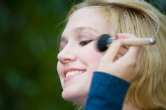 Beautiful Yong Blonde Girl with Blue Eyes Putting on Makeup royalty free stock photos