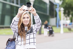 Beautiful youn woman takes pictures with the camera in the street Royalty Free Stock Photos
