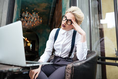 Beautiful younf tired blonde woman working with laptop outdoors Royalty Free Stock Images