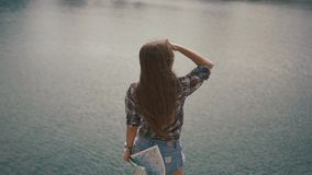 Beautiful young active backpacker girl checking with map near water surface of mountain lake at sunny day stock video