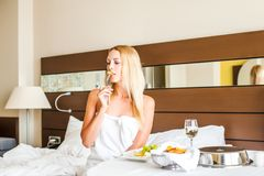 Woman have breakfast in badroom in hotel. Beautiful young adult blond Woman model have breakfast dinner or lunch in badroom in hotel royalty free stock image
