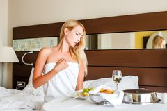 Woman have breakfast in badroom in hotel. Beautiful young adult blond Woman model have breakfast dinner or lunch in badroom in hotel stock image