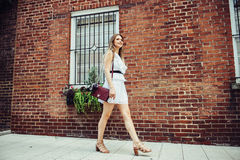Beautiful young adult happy student woman walking at university campus to study wearing white sexy dress. Stock Photography
