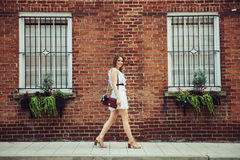 Beautiful young adult happy student woman walking at university campus to study wearing white sexy dress. Royalty Free Stock Photos