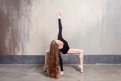 Beautiful young adult long haired woman dancing in studio stock photo