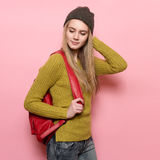 Beautiful young adult student girl with backpack ready to go study. Happy smiling Woman wearing casual outfit posing near pink wal Royalty Free Stock Image