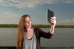 Beautiful young adult woman taking picture of herself, selfie shot with phablet leaning back metal fence in front of Royalty Free Stock Photography