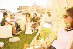 Beautiful young adults socialising together outdoors on an urban rooftop. Happy group of attractive friends drinking and socialising outdoors on a green lawn Royalty Free Stock Photos