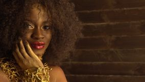 Beautiful young african american female model with gold glossy makeup. Face art. Black studio background.  stock footage